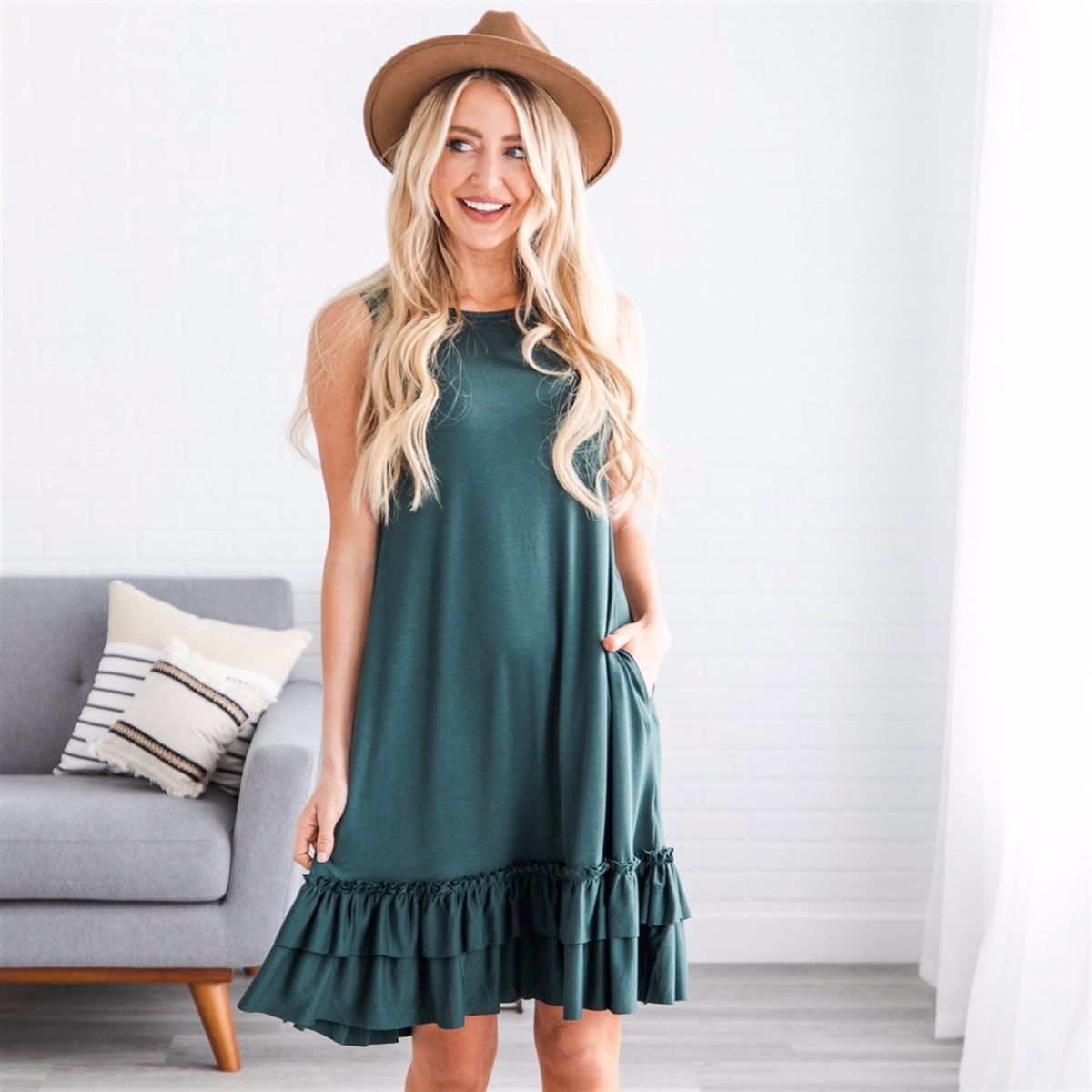 Summer dresses: a woman wearing a brown hat and a jade green sleeveless dress