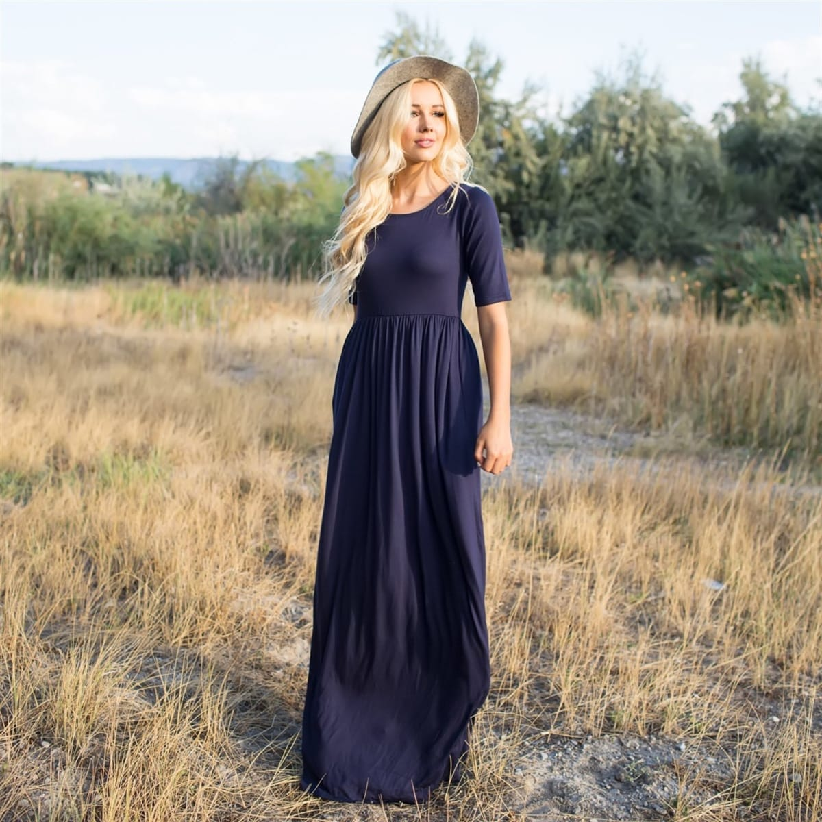 Summer dresses: woman wearing a hat and a navy blue maxi dress